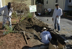 Institute members digging a hole for happiness in a family's front yard.