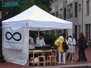 A booth bearing the logo of the Institute for Infinitely Small Things with Institute members and members of the public.